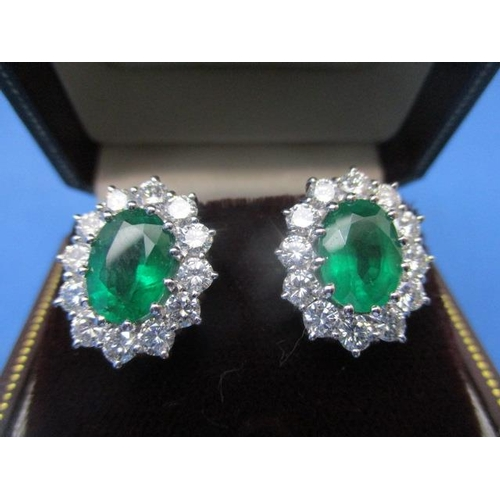 60 - A pair of 18ct white gold earrings each set with an emerald within a band of twelve diamonds, 8.6g...