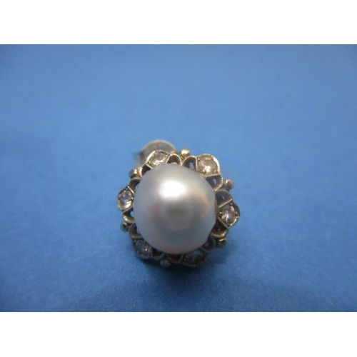 67 - A pair of white and yellow gold coloured metal earrings, set with a central pearl and six diamonds, ...