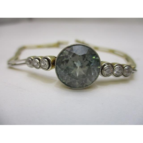 82 - An 18ct yellow gold and platinum bracelet set with an aquamarine, flanked by six graduated diamonds,...