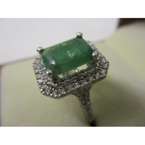 342 - An 18ct white gold ring set with a emerald cut emerald within two bands of diamonds and diamonds to ...