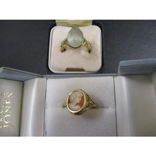 19 - Two gold coloured rings, one set with an aquamarine coloured stone and the other a cameo...