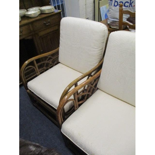 12 - A cane two seater settee, together with a matching armchair and a similar swivel chair...