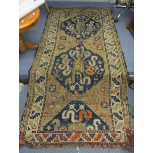 36 - A Caucasian rug with twin medallions, S shaped and geometric motifs on a blue and beige ground, 97