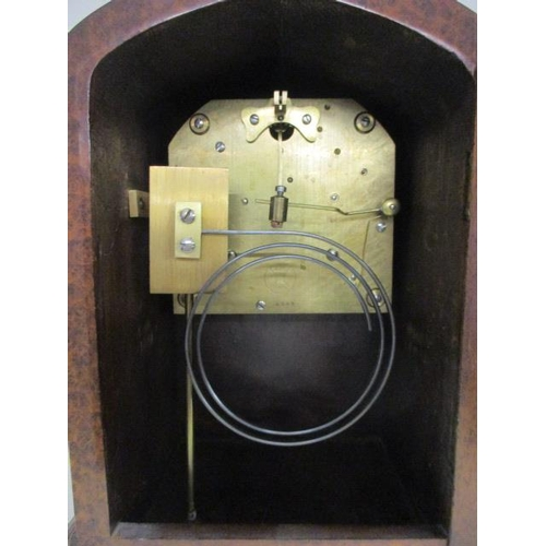 44 - An early 20th burr maple cased mantle clock with a key...