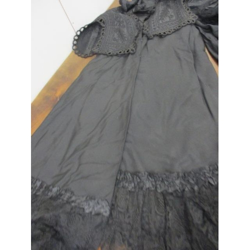 10 - A Victorian morning skirt and matching cape, an early 20th century black sleeveless evening dress wi...