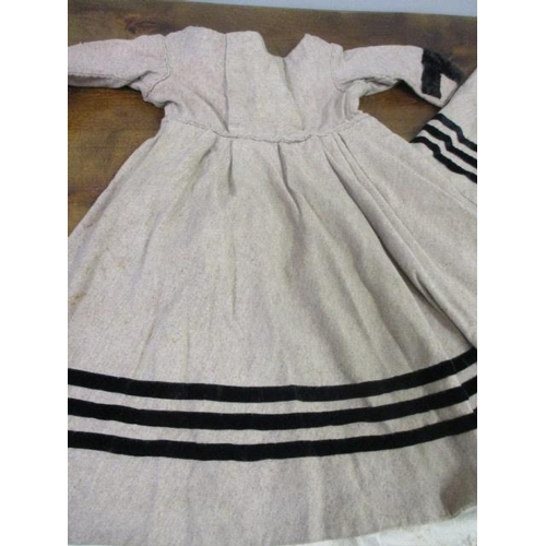 11 - An Edwardian woollen girls dress with matching cape, together with a grey quilted child's cape...