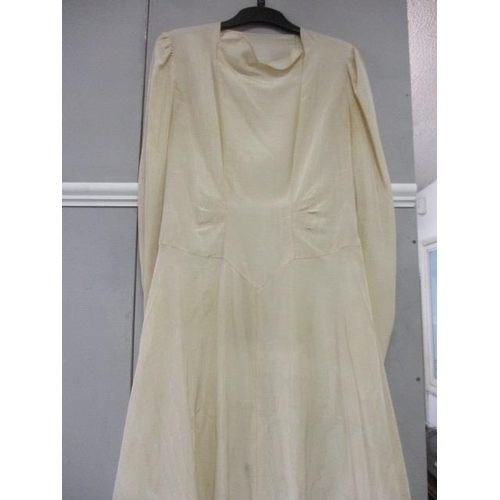 6 - An early 20th century cream wedding dress incorporating a train to the rear...