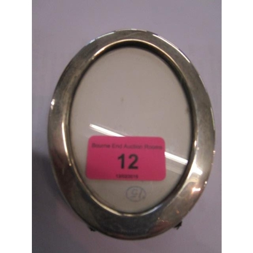 12 - An oval silver photo frame...