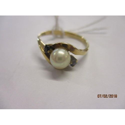 14 - A yellow metal ring set with a central pearl flanked by two small sapphires, marks rubbed, total wei...