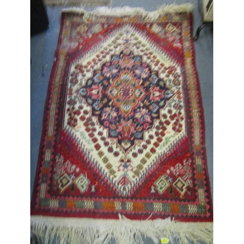 31 - A group of four hand woven Persian and Turkish rugs, to include a red ground Bokhara rug with elepha...