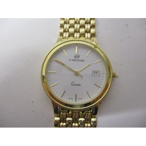 21 - A W Bruford a gents quartz 14ct wristwatch. The white dial having date aperture at 3, baton markers ...