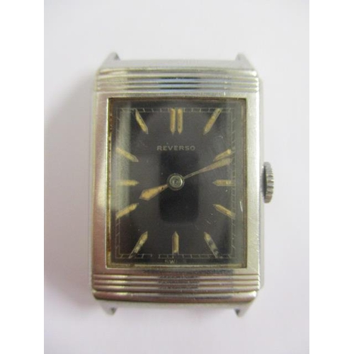 3 - An early 1930s original Reverso gents, manual wind, stainless steel wristwatch. The black dial havin...