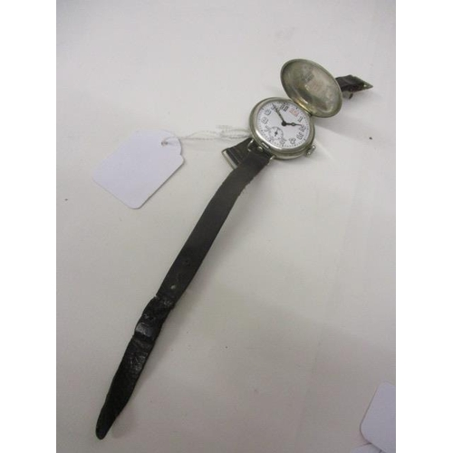 32 - An early 20th century gents, manual wind, nickel cased trench watch. The white enamel dial having Ar...
