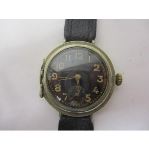 26 - An early 20th century, nickel cased Officers trench watch. The black dial having Arabic numerals and...