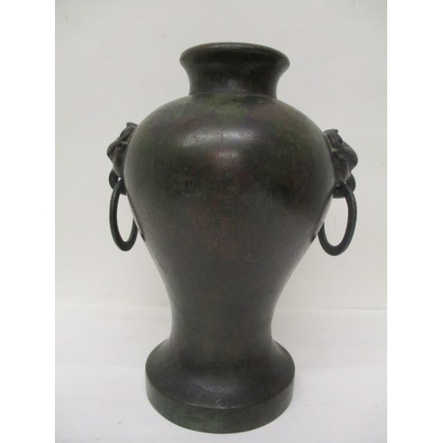 14 - A Chinese Ming style dark brown and green patinated bronze baluster vase with twin ring mask handles...