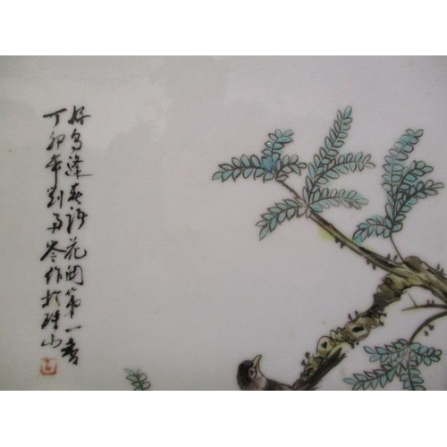 4 - A pair of 20th century Chinese plaques, each decorated with birds on a branch, above rocks and flowe...