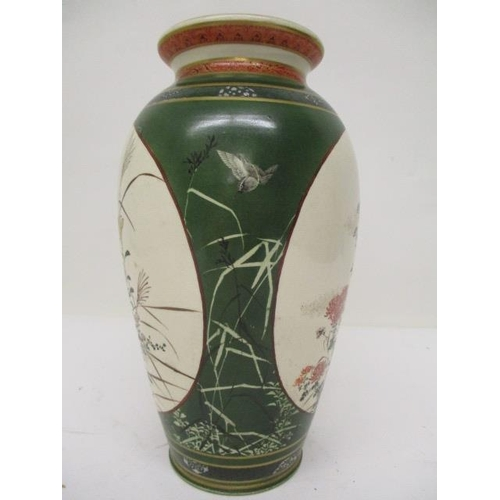 5 - A late 19th century Satsuma vase of baluster from decorated with two panels of flowers, on a green g...