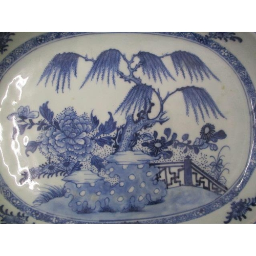 7 - A mid/late 18th century Chinese blue and white oval dish decorated with a tree, rocks and flowers by...