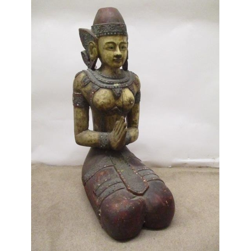 23 - A 20th century Thai painted, carved wooden Buddha kneeling with her hands together, wearing a hat wi...