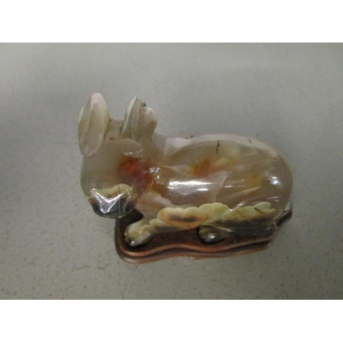 30 - A Chinese carved chalcedony model of a rabbit on a wooden base, probably early to mid 20th century A...