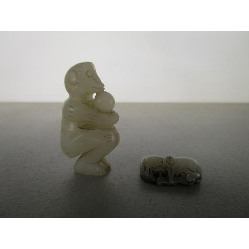 31 - Two Chinese pale green jade carvings, probably 19th century, one a monkey squatting, holding a singl...