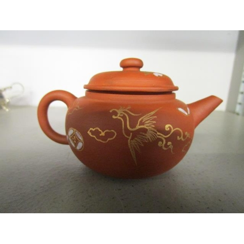 33 - A Chinese terracotta small teapot with gilt phoenix and floral decoration having white enamel highli...