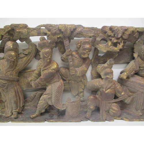 34 - A 20th century Chinese red painted and gilt carved pine panel of an allegorical scene with six figur...