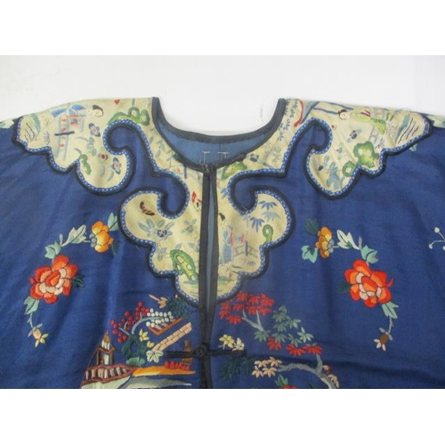 35 - An early 20th century Chinese blue silk and embroidered gown with panels of figures in garden settin...