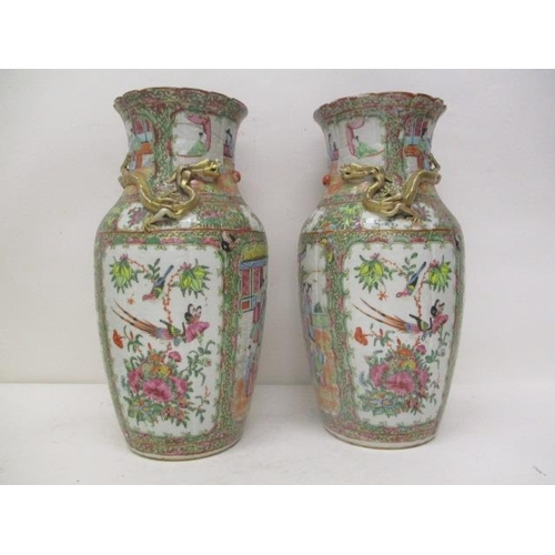 39 - A pair of late 19th century Chinese Canton vases with a  folded neck, decorated with a dragon in rel...