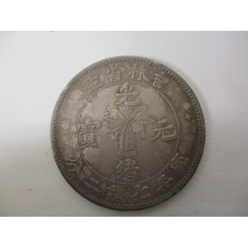 44 - A Chinese silver coloured coin, one side inscribed Kirin Province Candarins and a dragon with text a...
