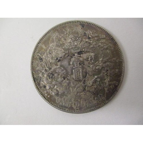 45 - A Chinese silver coloured one-dollar coin with a dragon, clouds and text to one side and text to the...