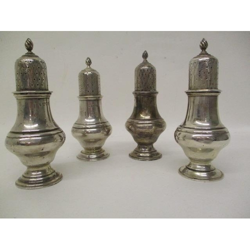 11 - A matched set of four early 20th century silver pepper pots by Haseler Brothers, London 1910-1913, m...