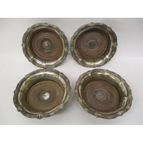 12 - A set of four George IV silver wine bottle coasters by Samuel Walker & Co, Sheffield 1830 with lobed...