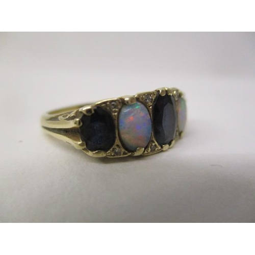 28 - A 9ct gold ring set with three sapphires and two opals, in an ornate scrolled setting, size O, 4.5g...