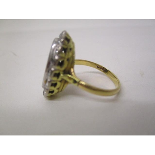 33 - An 18ct gold ring set with an opal, approximately 15mm x 7mm within a border of thirteen diamonds, s...