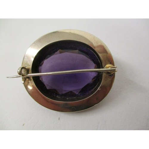 38 - A Victorian gold coloured metal brooch set with an amethyst, approximately 25mm x 20mm within a bord...