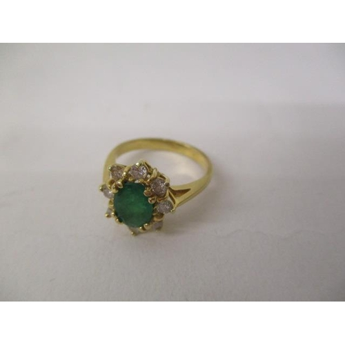 39 - A gold coloured metal ring set with an emerald, surrounded by eight diamonds, stamped 750, size J/K,...