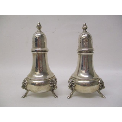 4 - A pair of mid 20th century sterling silver pepper pots with acorn finials and tapered, bulbous bodie...