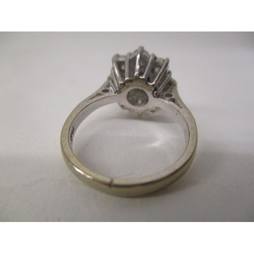 42 - A white gold coloured metal ring set with a central sapphire, surrounded by eight diamonds, stamped ...