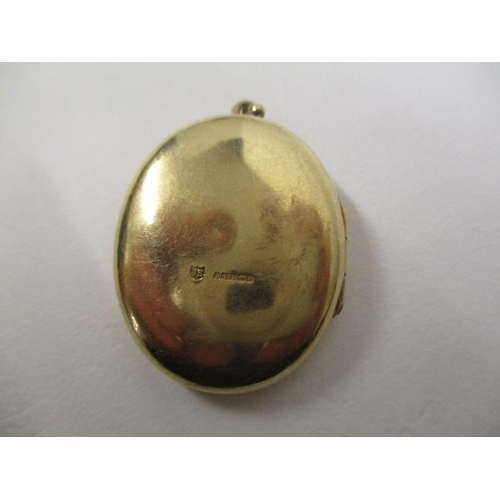 45 - A 9ct gold oval locket with flowers engraved to the front, on a suspension ring, 9g...