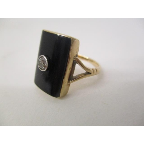 25 - A gold coloured ring set with a central diamond on a black curved tablet and panelled back, size N, ...