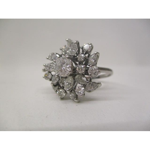 26 - A white metal ring set with a central diamond, approximately 0.48cts, surrounded by twenty one irreg...