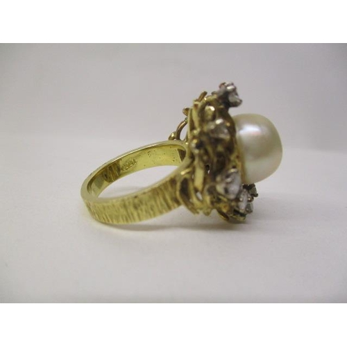 27 - A gold coloured ring set with a central pearl, approximately 11mm, surrounded by twelve irregular se...