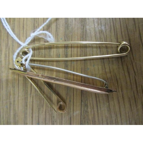 16 - Three 9ct gold brooches/tie pins, one fashioned as a torpedo...