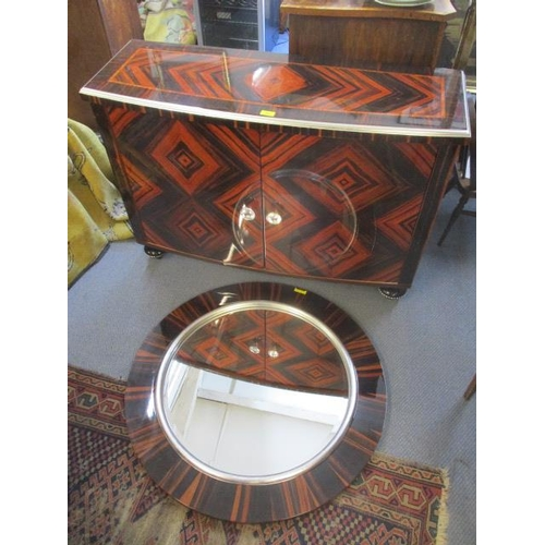 25 - A modern exotic wood veneered, bow fronted cabinet with twin doors, on black painted, turned feet an...