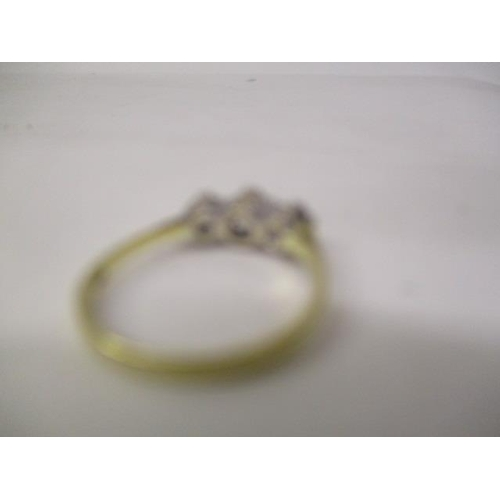 32 - An 18ct gold and platinum coloured three stone diamond ring, the central stone approximately 0.3ct, ...