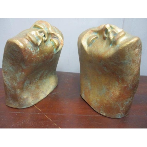 1 - A pair of contemporary bookends in the form of painted pottery heads...