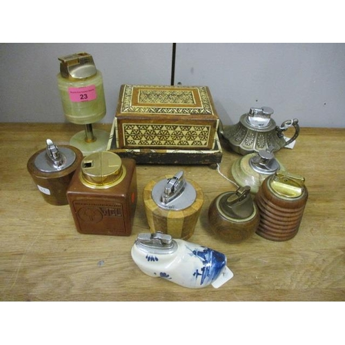 23 - A bone inlaid cigarette box together with mixed table lighters...