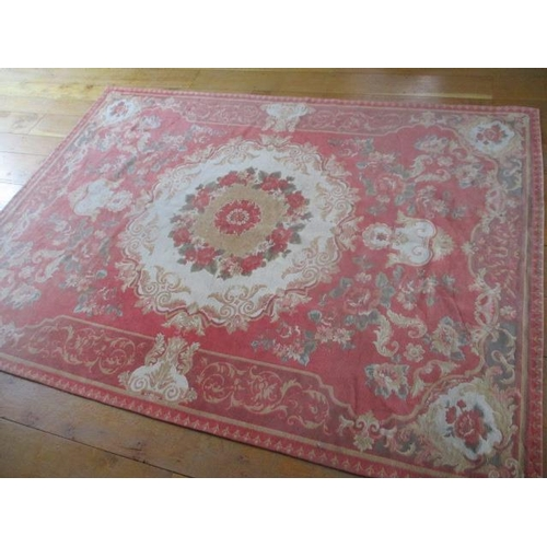40 - An Italian Society Aubusson rug with a coral pink background and floral detail, 67