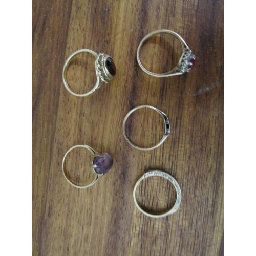 12 - A group of 9ct gold and gem set rings to include a garnet ring and an amethyst ring, along with a di...